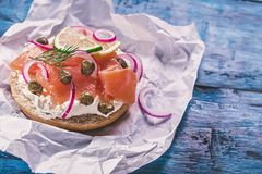 Salmon sandwich on blue. Bun with cream cheese. smoked salmon, red onion, capers and lemon on rustic blue table Stock Images