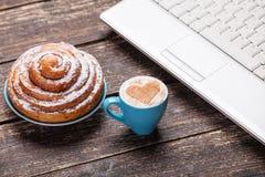 Bun croissant and cup near laptop Stock Photos