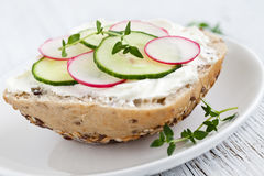 Bun with cucumber and radish. Bread with cucumber and radish on a plate Stock Photos
