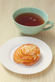 Bun and cup of tea on tray Stock Photos