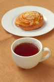 Bun and cup of tea on tray Royalty Free Stock Photo