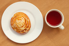 Bun and cup of tea on tray Stock Photography