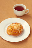 Bun and cup of tea on tray Royalty Free Stock Photos