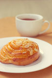 Bun and cup of tea on tray Royalty Free Stock Images