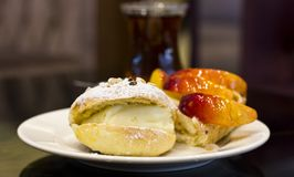 Bun with custard and powdered sugar. Peach pie in the glaze. Royalty Free Stock Photography