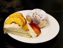 Bun with custard and powdered sugar. Peach pie in the glaze. Stock Images