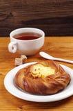 Bun with custard and tea Royalty Free Stock Photos