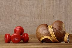 Bun dumbbells and tape measure. Small delicious dietary bun and yellow tape measure with two lottle red dumbbells as a symbol of diet lie on the table on brown Stock Image
