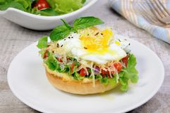 Bun with egg. Sandwich with vegetable filling and egg poached, sprinkled cheese Royalty Free Stock Photo