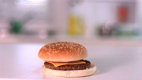 Bun falling on cheese burger in kitchen stock video footage