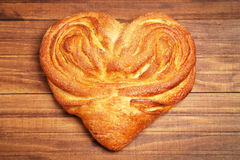 Bun in heart form with sugar. On wooden background Stock Image