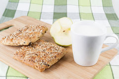 Bun with milk on wooden plank. Fresh breakfast Stock Images