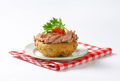 Bun with pate. Fresh bun with pate, cherry tomato and parsley on white plate and checkered dishtowel royalty free stock photo