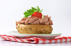 Bun with pate. Fresh bun with pate, cherry tomato and parsley on white plate and checkered dishtowel stock photo