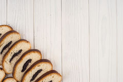 Bun with poppy seeds on a kitchen napkin and an old wooden table Stock Images