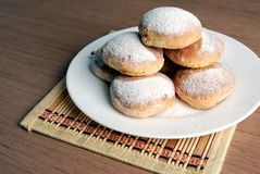 Bun with powdered sugar on a wooden table Royalty Free Stock Photo