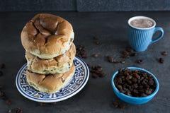 Bun with raisins, Dutch krentenbol or rozijnenbol on blue plate stock photography