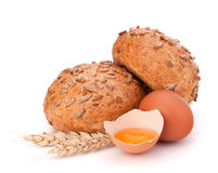 Bun with seeds and broken egg Stock Photo