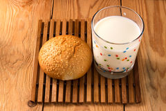 Bun with sesame seeds and a glass of milk. Bun with sesame seeds and a transparent glass of milk on wooden background Royalty Free Stock Image