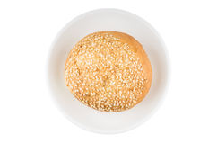 Bun with sesame seeds on glass saucer. Top view Royalty Free Stock Photos