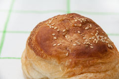 Bun with sesame seeds on the kitchen tablecloth Royalty Free Stock Photos