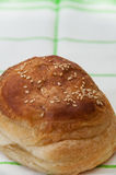 Bun with sesame seeds on the kitchen tablecloth Stock Photo