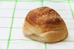Bun with sesame seeds on the kitchen tablecloth Stock Images