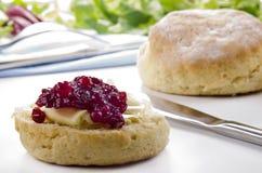 Bun spread with cranberry jam Royalty Free Stock Photo
