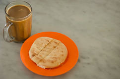 Bun and White Coffee. Toasted bun filled with butter served on plate with white coffee in glass on table royalty free stock photo