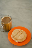 Bun and White Coffee. Toasted bun filled with butter served on plate with white coffee in glass on table royalty free stock image