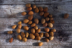 Bunch of almonds unshelled, badam, forest fruit harvest on wood Stock Images