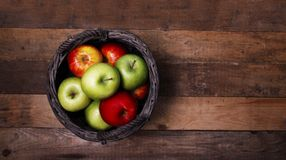 A bunch of apple in a basket. On a wooden background Royalty Free Stock Image