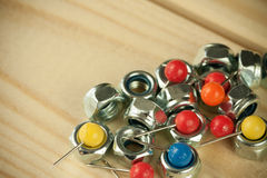 Bunch of arranged pins with vivid colorful pinheads and industrial metal nuts screws Stock Images