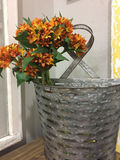 A bunch of artificial orange flowers in container Stock Photo