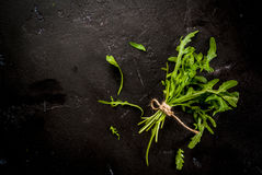 Bunch of arugula. Bunch of salad leaves greenery, arugula, black concrete stone table, top view stock photos