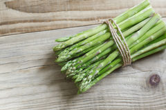 Bunch of asparagus. Bunch of fresh green asparagus bandaged with a rope. Fresh asparagus on a wooden table in a rustic style. Low key, close-up royalty free stock photo