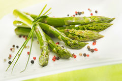 Bunch of asparagus on a plate. Bunch of asparagus with spices on a plate royalty free stock image