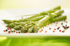 Bunch of asparagus on a plate. Bunch of asparagus with spices on a plate stock photo