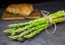 A bunch of asparagus with roasted pork tenderloin on the wooden cutting board Stock Photo