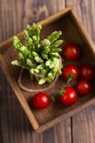 Asparagus and tomatoes top view. Bunch of asparagus and some cherry tomatoes in a wooden box, overhead shot stock photos