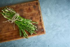 Bunch of asparagus on wooden cutting board Stock Images