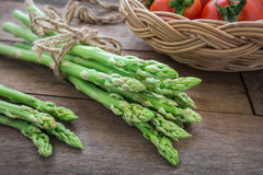 Bunch of asparagus on wooden table and tomato in basket. Bunch of asparagus on wooden table and tomato in wicker basket Stock Photography