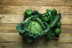 Bunch Assortment of Fresh Organic Green Vegetables Savoy Cabbage Zucchini Cucumbers Bell Peppers Avocados in Trey on Aged Wood. Bunch Assortment of Fresh Organic Stock Photo