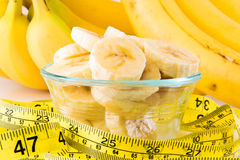 A bunch of bananas. With a bowl of sliced bananas  on a white background with the concept of diet showing the measuring tape Stock Images