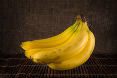 A bunch of bananas. Bunch of bananas with a burlap background sitting on bamboo stock image
