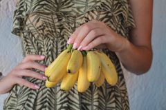 Bunch of bananas in a girl's hand Royalty Free Stock Images