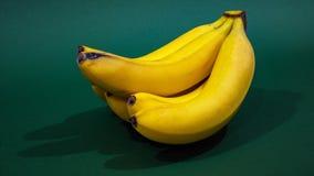 A bunch of bananas on a green background stock photos