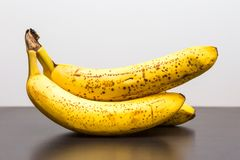 Bunch of bananas lying on dark wooden table Stock Images