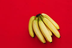 Bunch of bananas on red  background. Fresh organic Banana, Fresh bananas on kitchen table Royalty Free Stock Photography