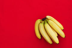 Bunch of bananas on red   background. Fresh organic Banana, Fresh bananas on kitchen table Royalty Free Stock Images